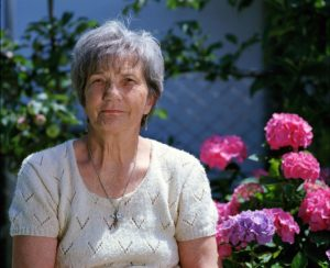 Frau vor Blumenbeet