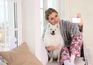 Frau mit Hund am Fenster