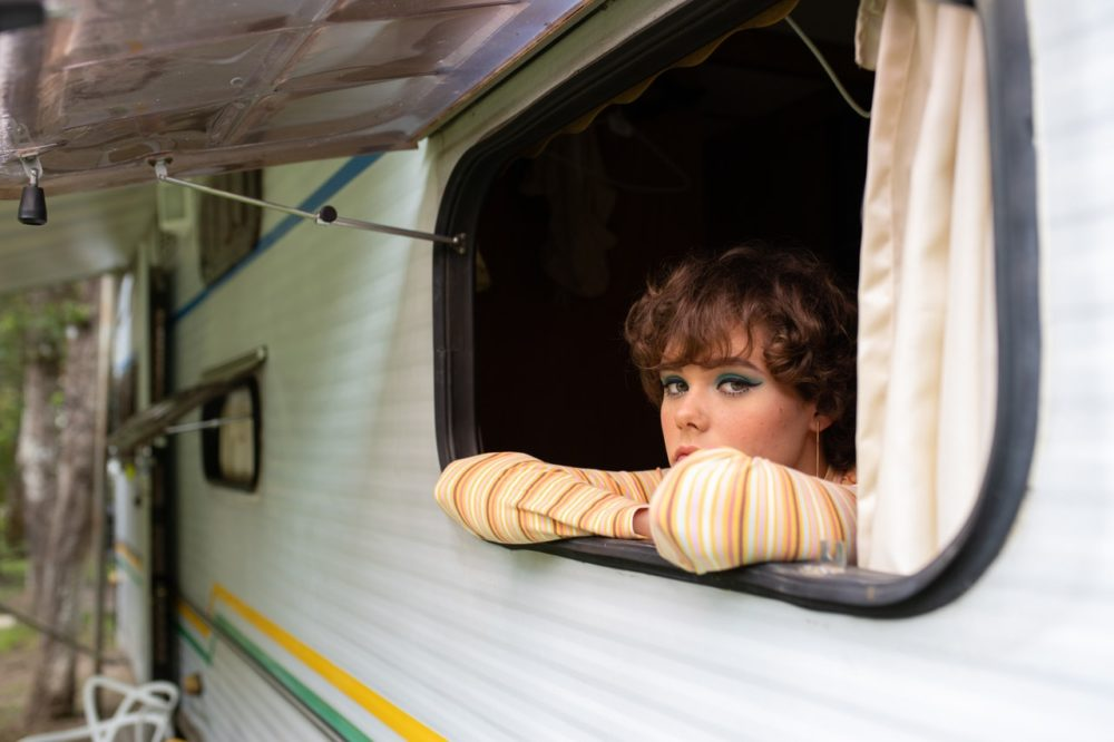 Frau schaut aus Wohnwagen