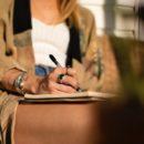 Frau sitzt und schreibt