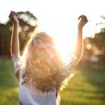 Frau auf Wiese in der Sonne