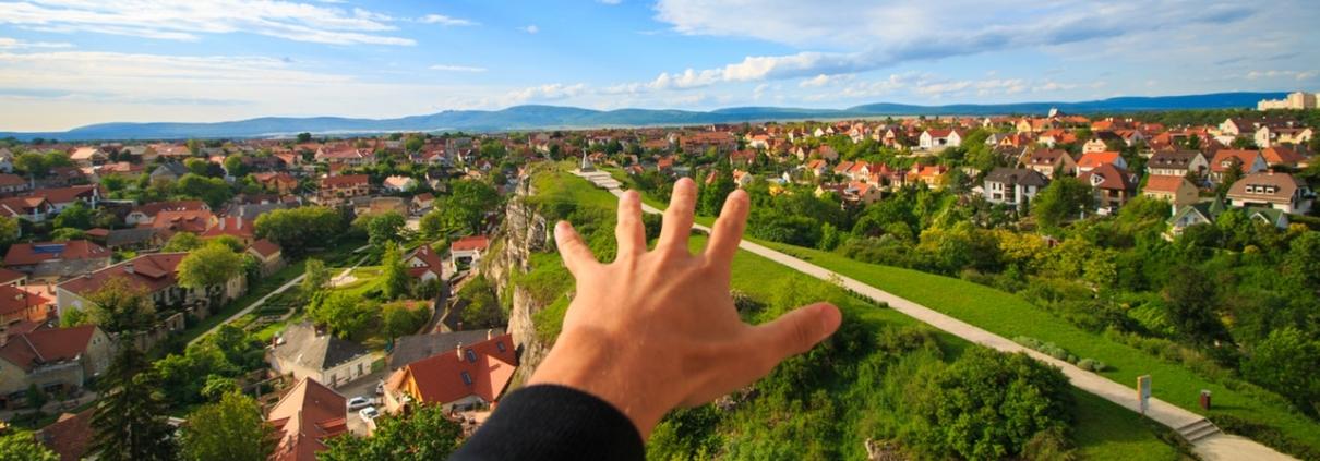 Hand vor einem Haus, vor Häusern